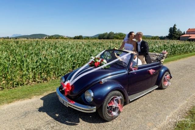 couple de mariés dans leur voiture se faisant un bisous