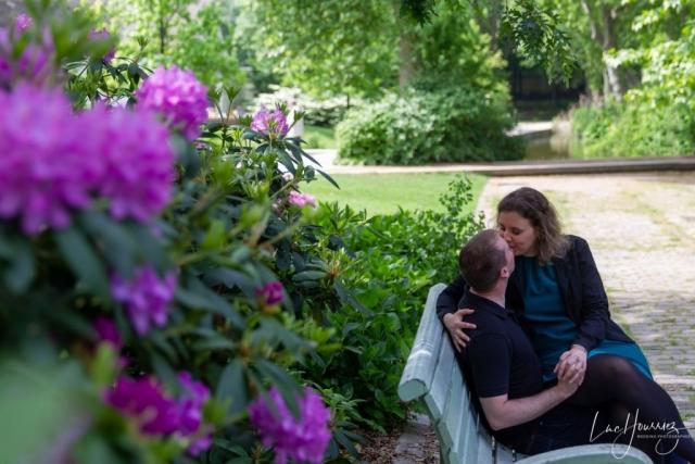 couple se faisant un bisous sur un banc à bercy village