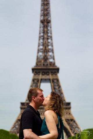 couple s'embrassant devant la tour eiffel
