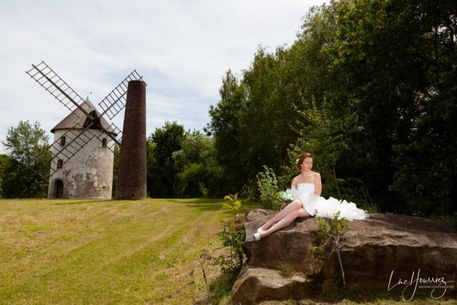 mariée assis sur un rocher devant un moulin
