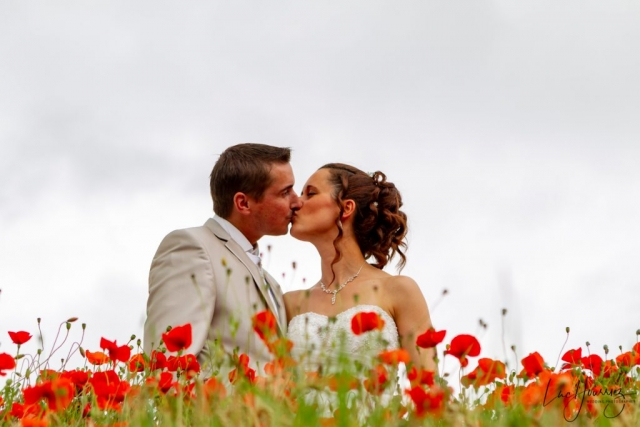 mariés se faisant un bisous dans un champ de coquelicot