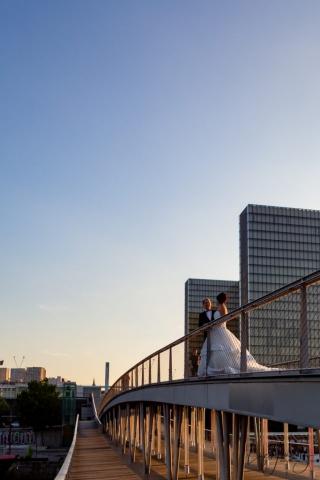 mariés sur un pont à paris pendant un couché de soleil