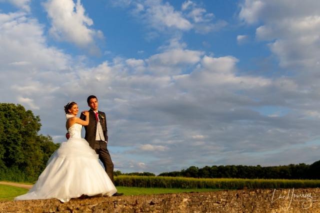 photo de couple mariage sur un muret au coucher du soleil